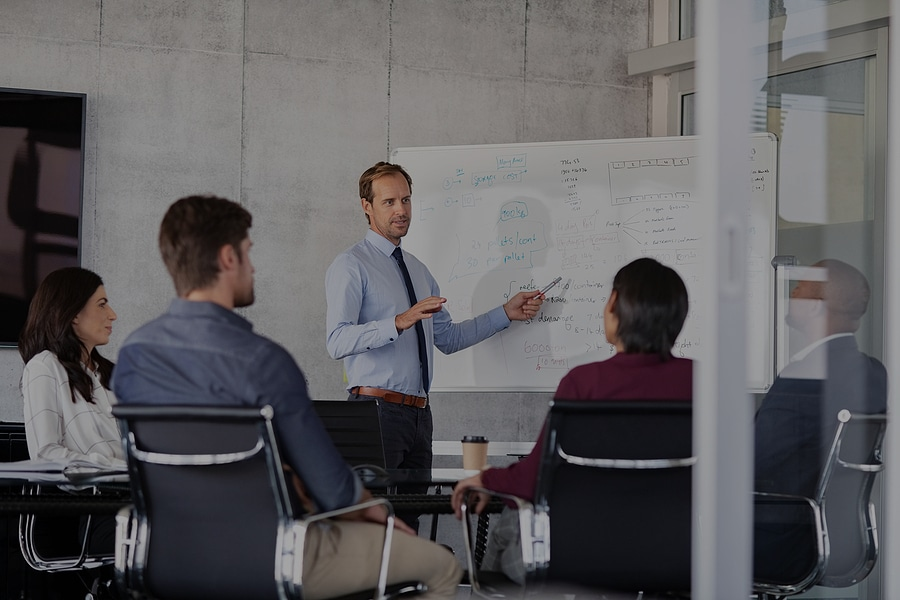 Mature businessman giving presentation to his colleagues in mode